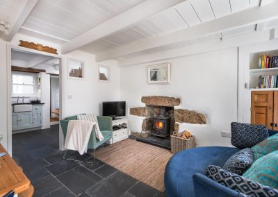 Living room with view of woodburner, sofa and armchair